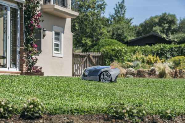 Automower 105 on lawn in sunshine with pink house in background
