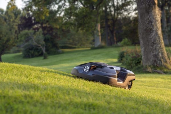 Automower 310 on sloped lawn with trees in background