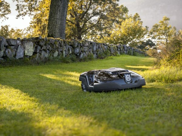 Automower 315 mowing lawn with stone wall in background