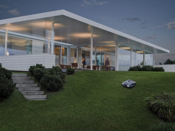 Automower 315X mowing sloped garden at dusk with house in background
