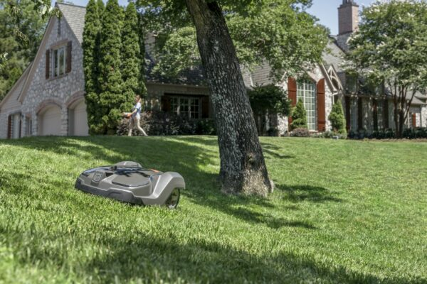 Automower 430X mowing sloped garden with house in background