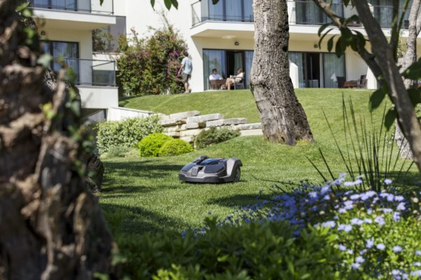 Automower 450X mowing garden with balconies and people in background