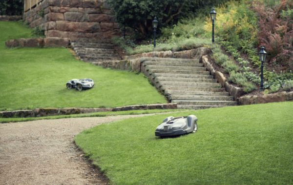 Automower 450X mowing sloped garden with 435X in background