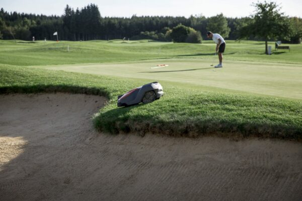 Commercial Automower on golf course with golfer in background