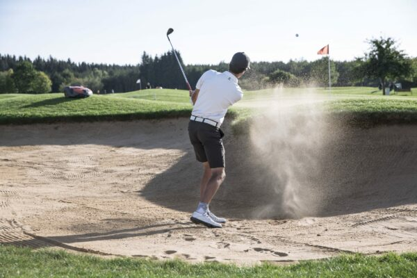 Man taking golf shot from bunker with Automower mowing green
