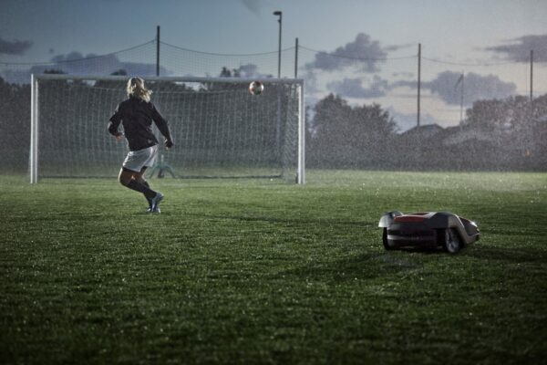 Automower 550 mowing football pitch in rain with woman kicking ball in background