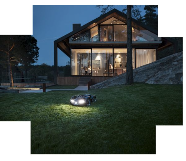 Automower 435X AWD mowing garden at night with people inside house in background